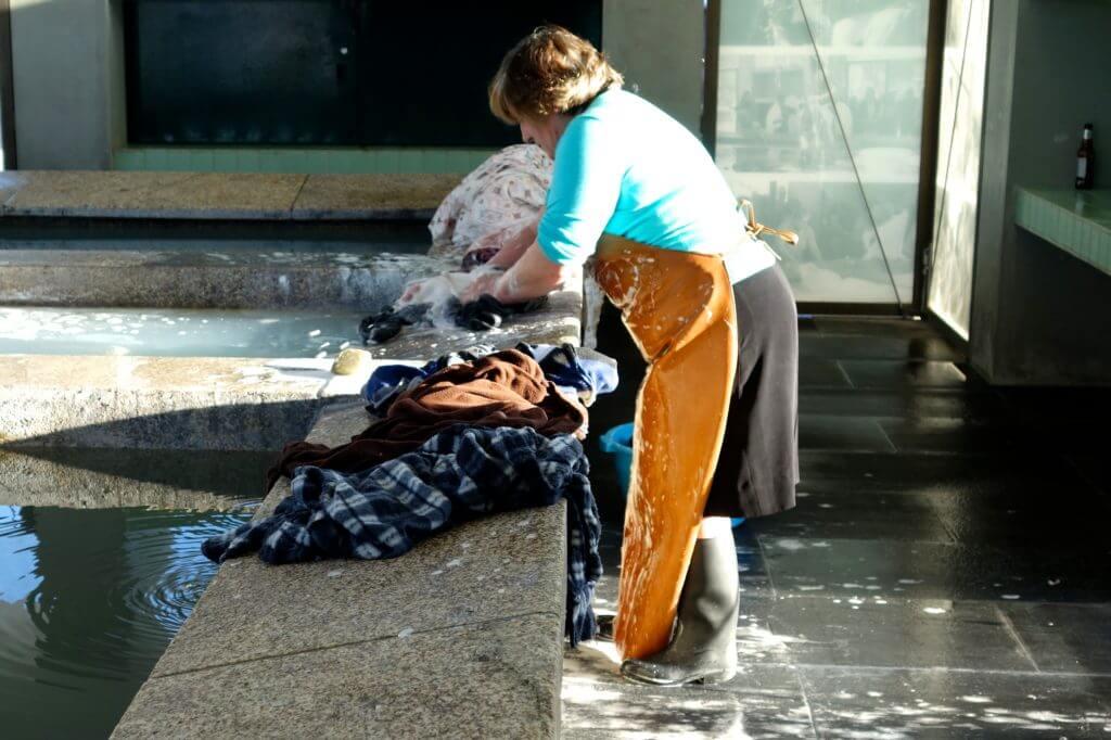 Frau bei der Arbeit im Lavadouro Público, dem öffentlichen Waschhaus von Afurada