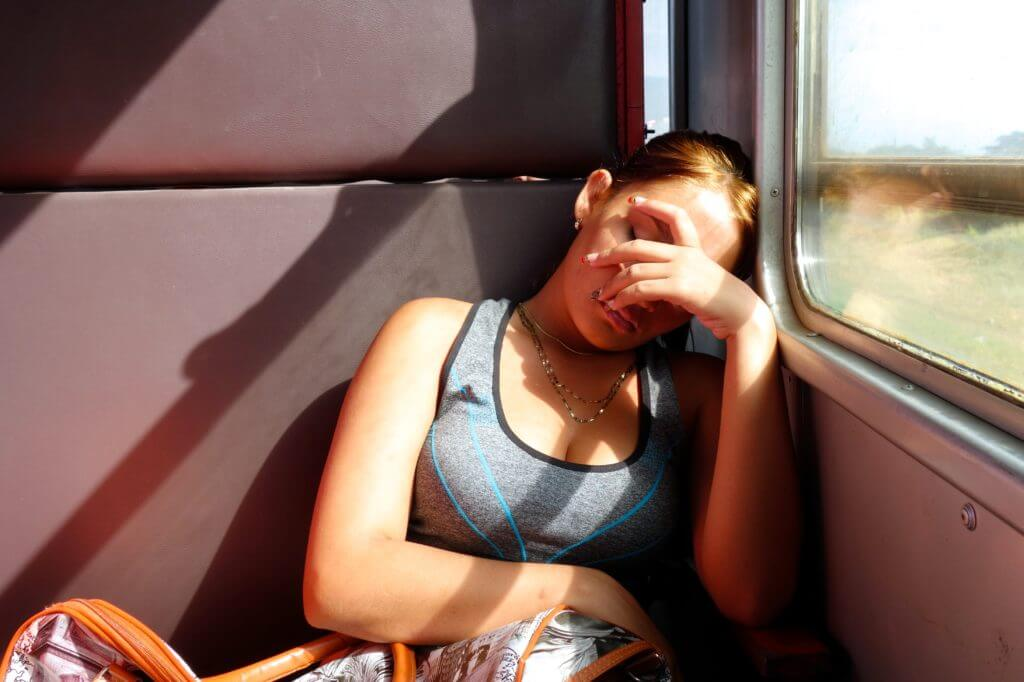 Zug fahren in Kuba. Müder weiblicher Fahrgast im Zug nach Holguín