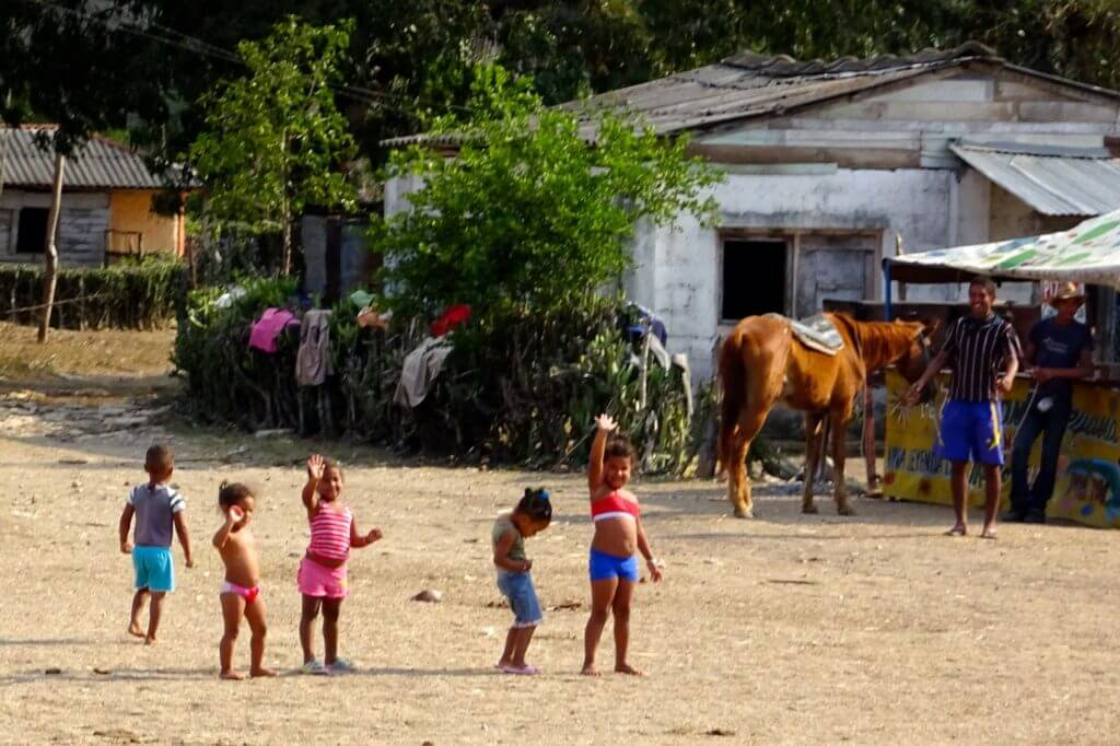 Zug fahren in Kuba. Winkende Kinder an der Bahnstrecke im Osten Kubas.