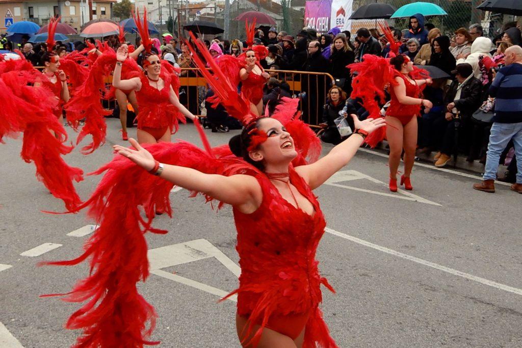 Karneval in Ovar, Portugal. Tänzerinnen in Rot trotzen dem Regen.