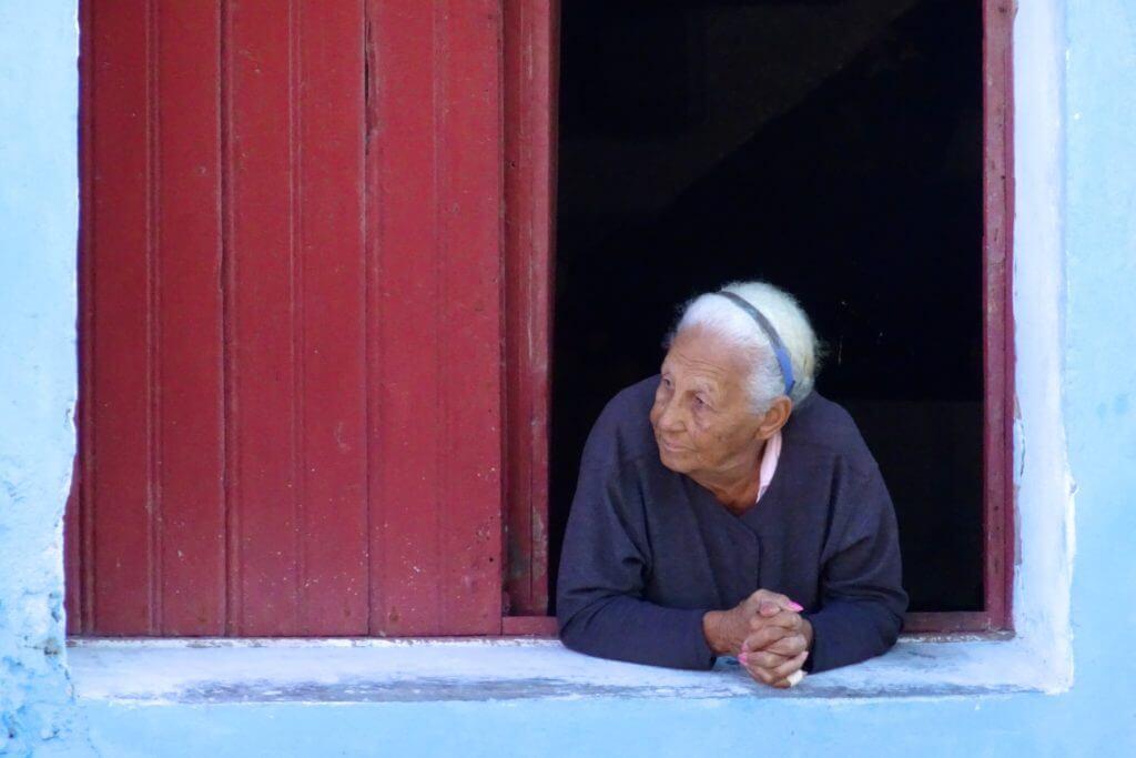 Gibara, Kuba. Eine alte Frau schaut neben der Zigarrenfabrik aus dem Fenster