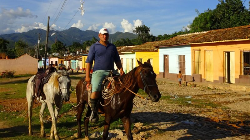 Trinidad, Kuba. Typische Szene: Reiter vor der Kulisse bunter alter Häuser.
