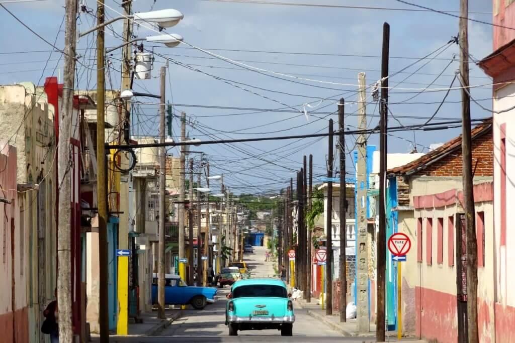 Holguín. Ein typisches Bild auf kubanischen Straßen: farbenfroher Oldtimer und Kabelsalat.