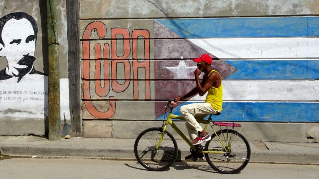 Santiago de Cuba. Radfahrer vor Wandmalerei.