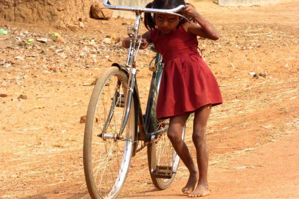 Straßenfotografie in Indien, unter dem Motto: Aller Anfang ist schwer. Kleines Mädchen mit großem Fahrrad.