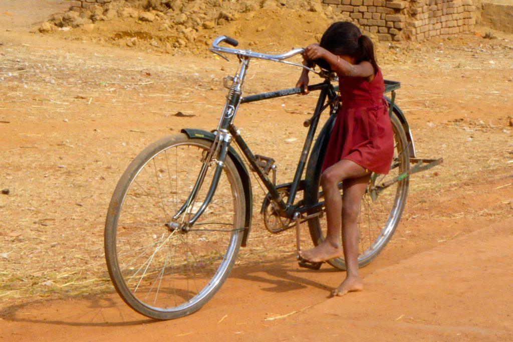 Straßenfotografie in Indien unter dem Motto aller Anfang ist schwer. Mädchen mit Fahrrad.