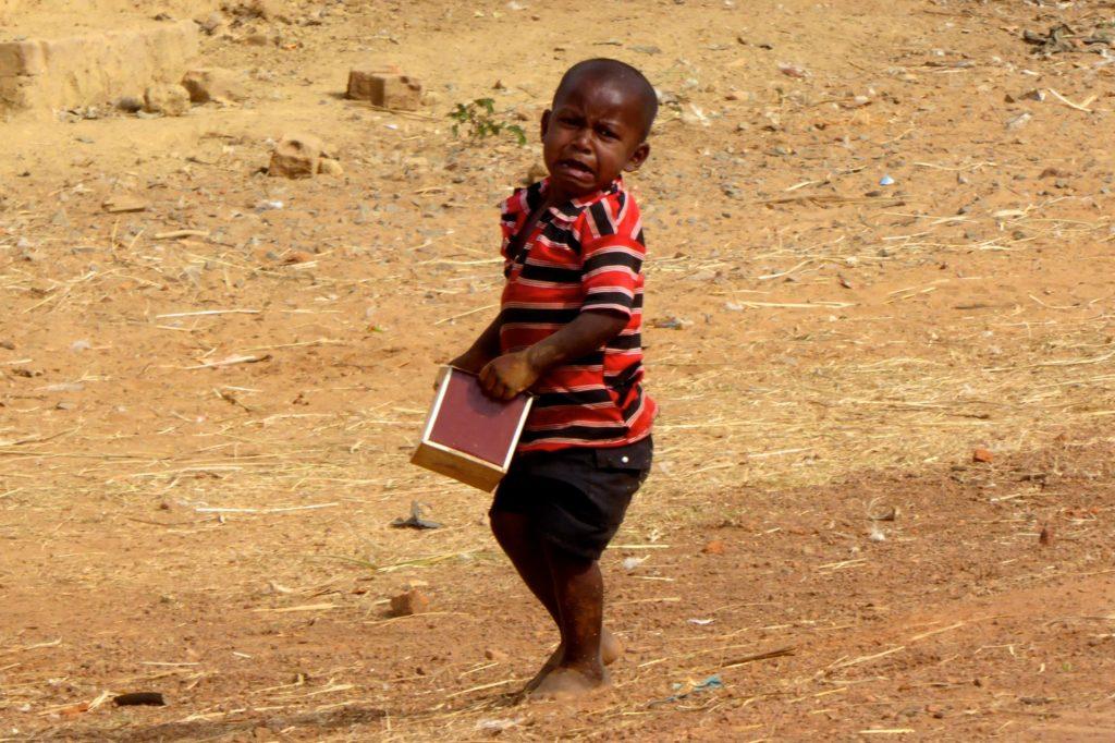 Straßenfotografie in Indien. Aller Anfang ist schwer. Kleiner Junge beim Kistenschleppen.