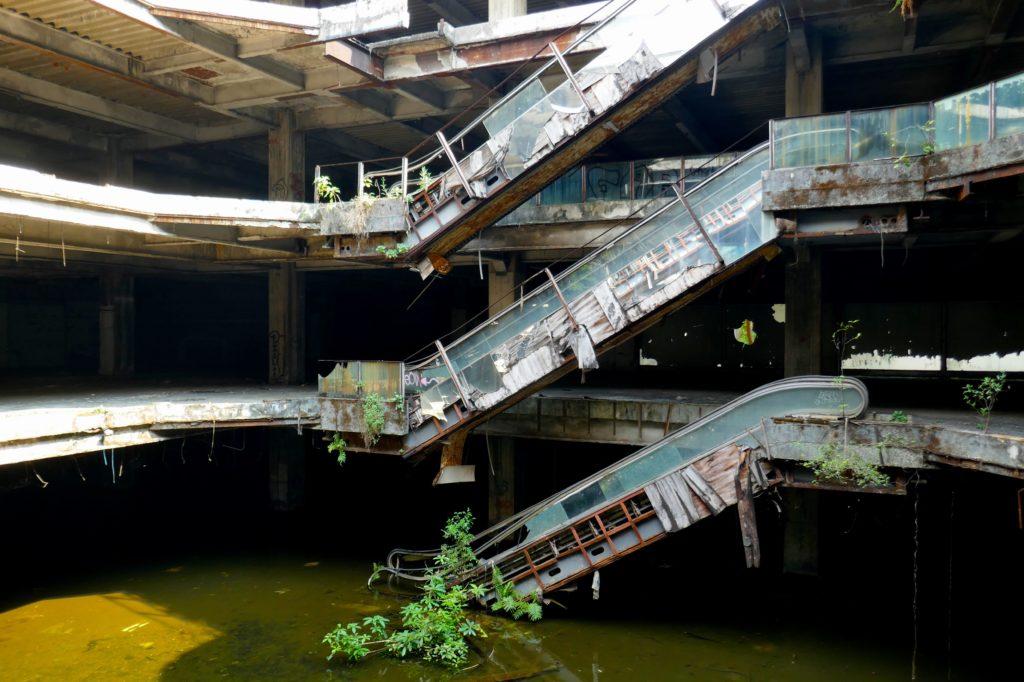 Lost Place New World Mall. Wasser im Untergeschoss, von oben fällt das Tageslicht in das Gebäude.