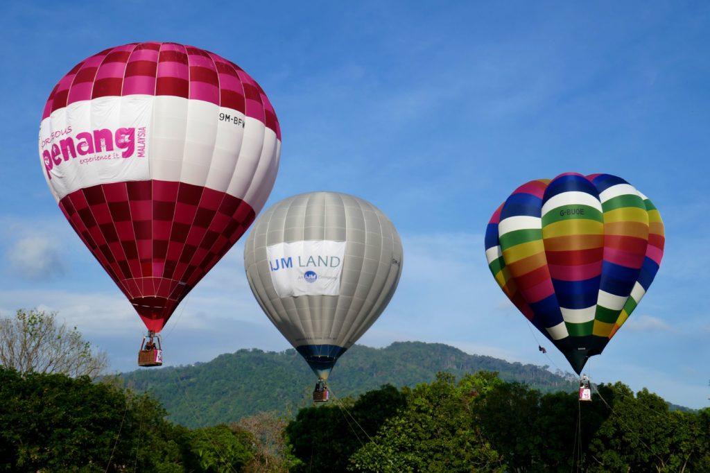 Penang Hot Air Balloon Fiesta in George Town. Drei Ballons schweben über dem Boden.