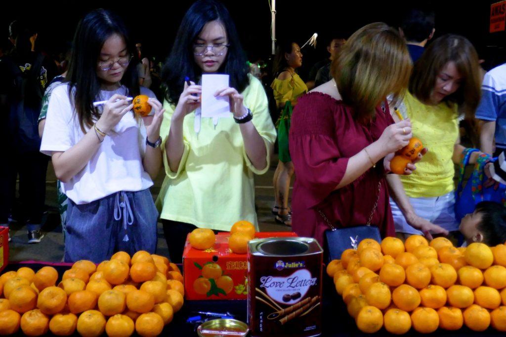 Chap Goh Meh, chinesischer Valentinstag in George Town, Malaysia. Sorgfältig werden die Früchte vor dem Werfen beschriftet.