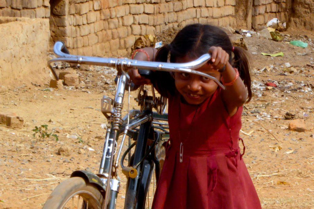 Straßenfotografie in Indien: Kleines Mädchen mit großem Fahrrad unter dem Motto aller Anfang ist schwer.