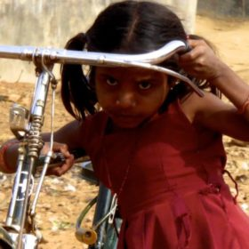 Street Photography in Indien. Kleines Mädchen mit großem Fahrrad.