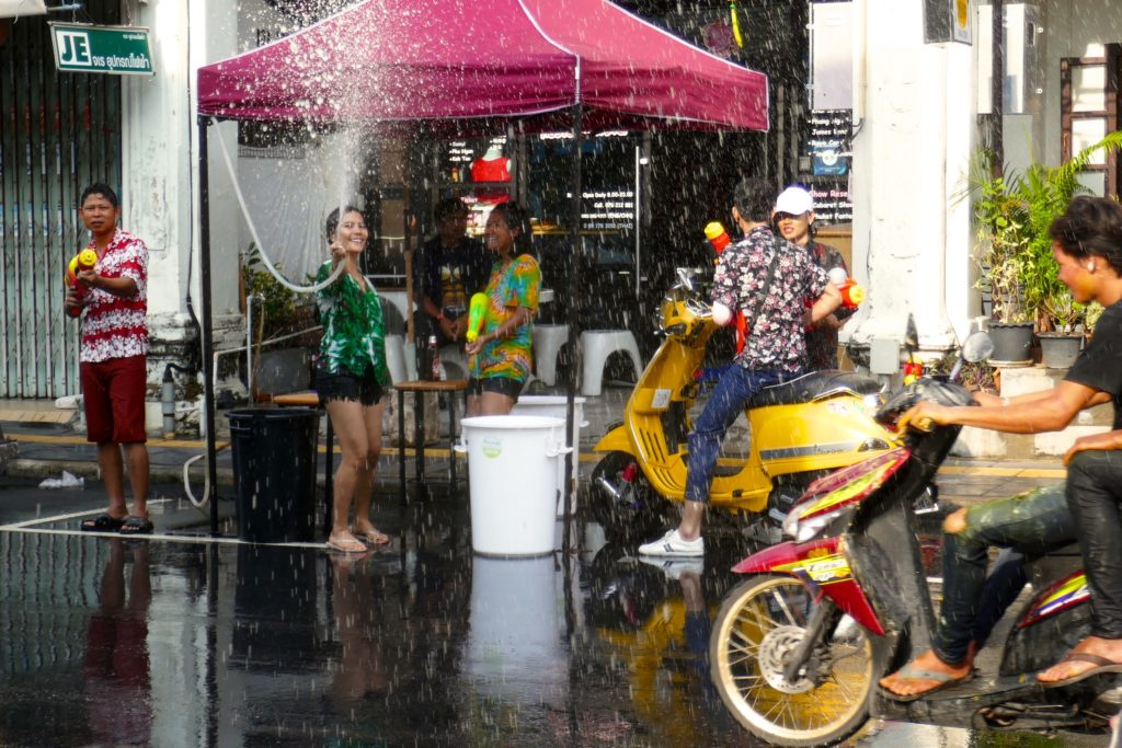Songkran in Phuket Town. Mit viel Wasser wird auf der Straße gespritzt.