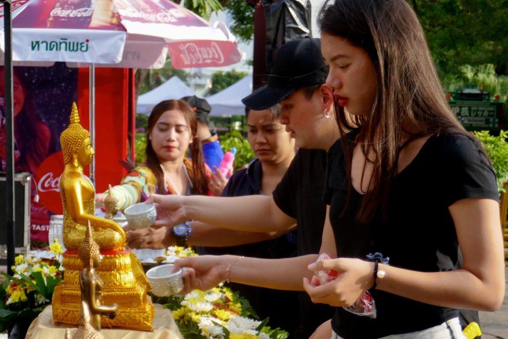 Songkran in Phuket Town. Traditionelles Ritual: Reinigung von Buddha-Statuen.