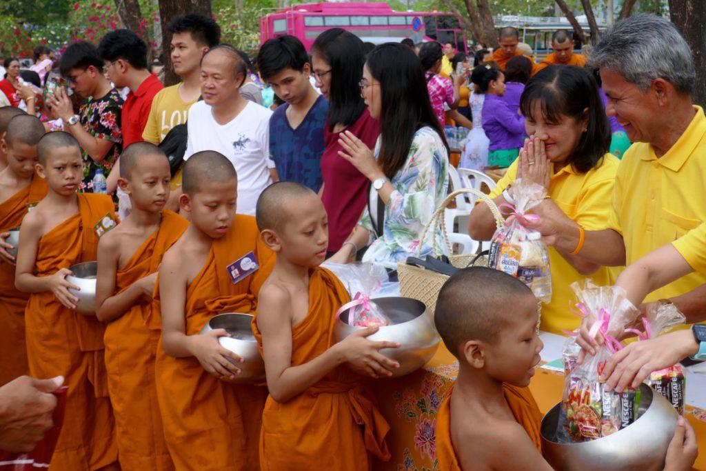 Tak Bat in Phuket Town. Übergabe von Almosen an die Nachwuchsmönche während der Songkran-Eröffnungszeremonie.