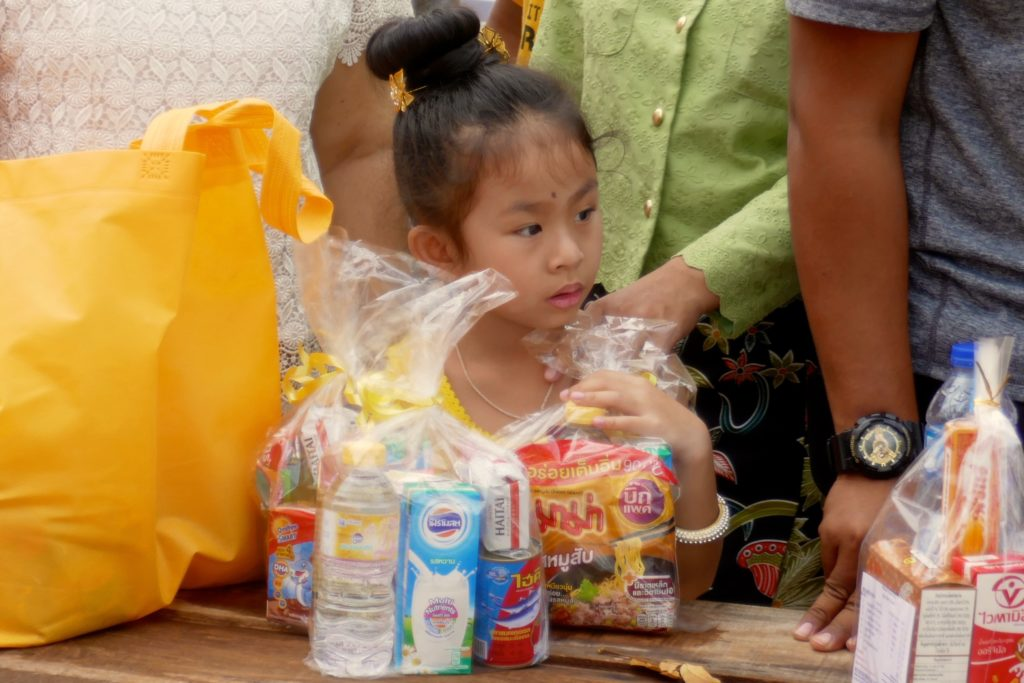 Tak Bat in Phuket Town. Kleine Besucherin wartet auf Mönche und Nonnen.