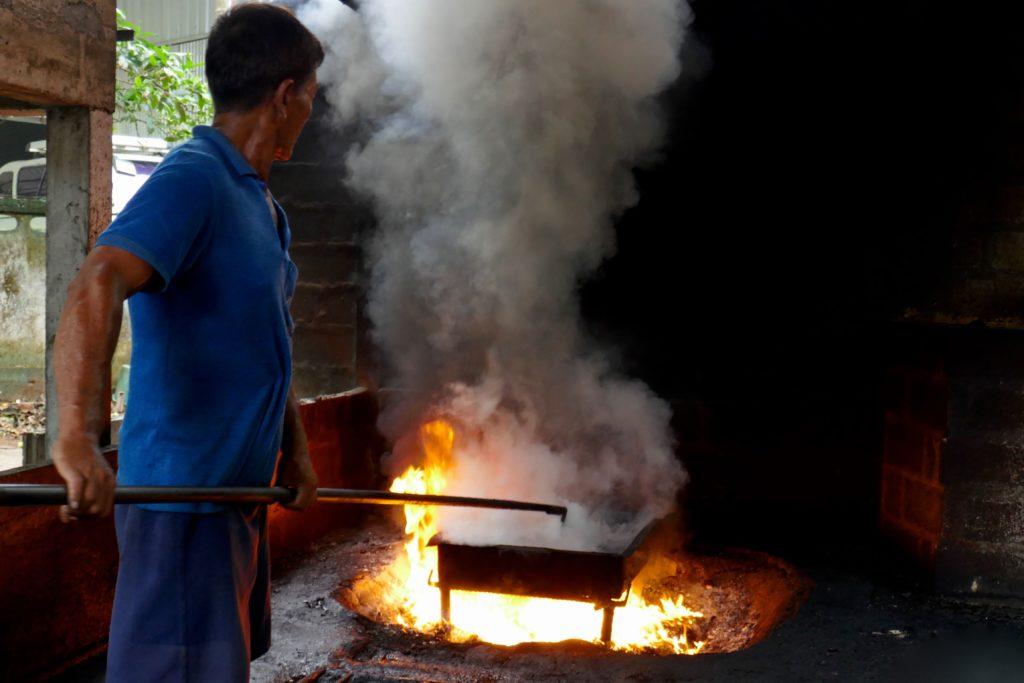 Menschen in Ramong. Mann beim Rösten von Cashewkernen.
