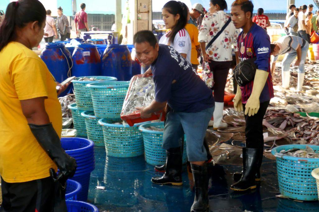 Kisten fliegen auf dem Fischmarkt von Ranong.