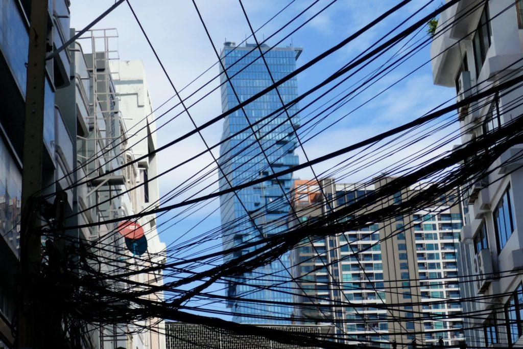 MahanaKhon Tower in Bangkok, eingerahmt von anderen Häusern, versteckt hinter Kabelgewirr.