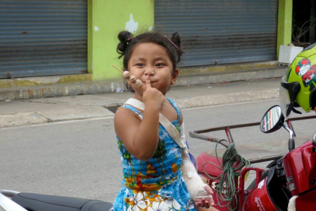 Menschen in Ranong. Kleines Mädchen sitzt Grimassen schneidend auf Motorrad.