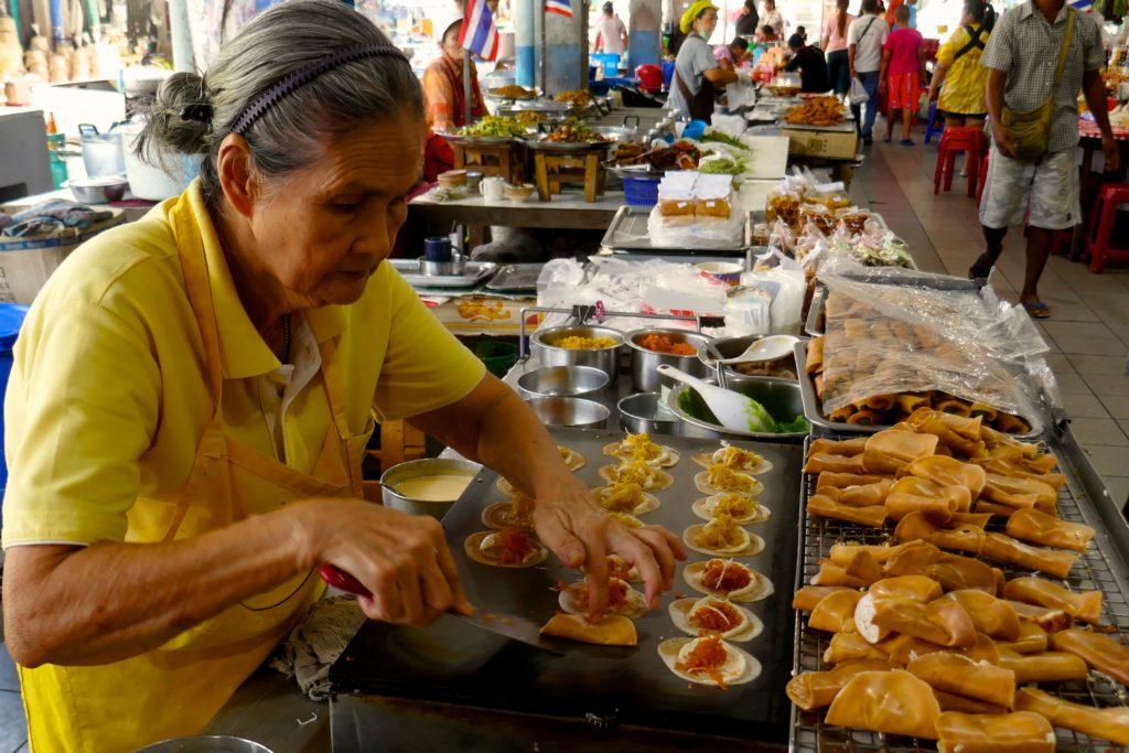 Menschen in Ranong. Zubereitung knuspriger Pfannkuchen auf dem Muang Ranong Municipal Food Market.