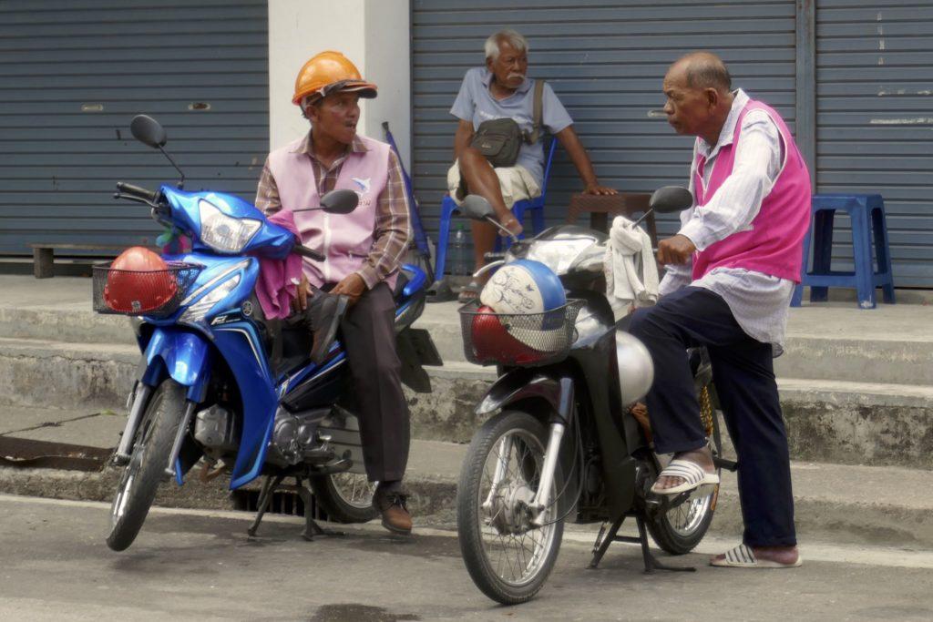 Menschen in Ranong. Wartende Motorrad-Taxifahrer.