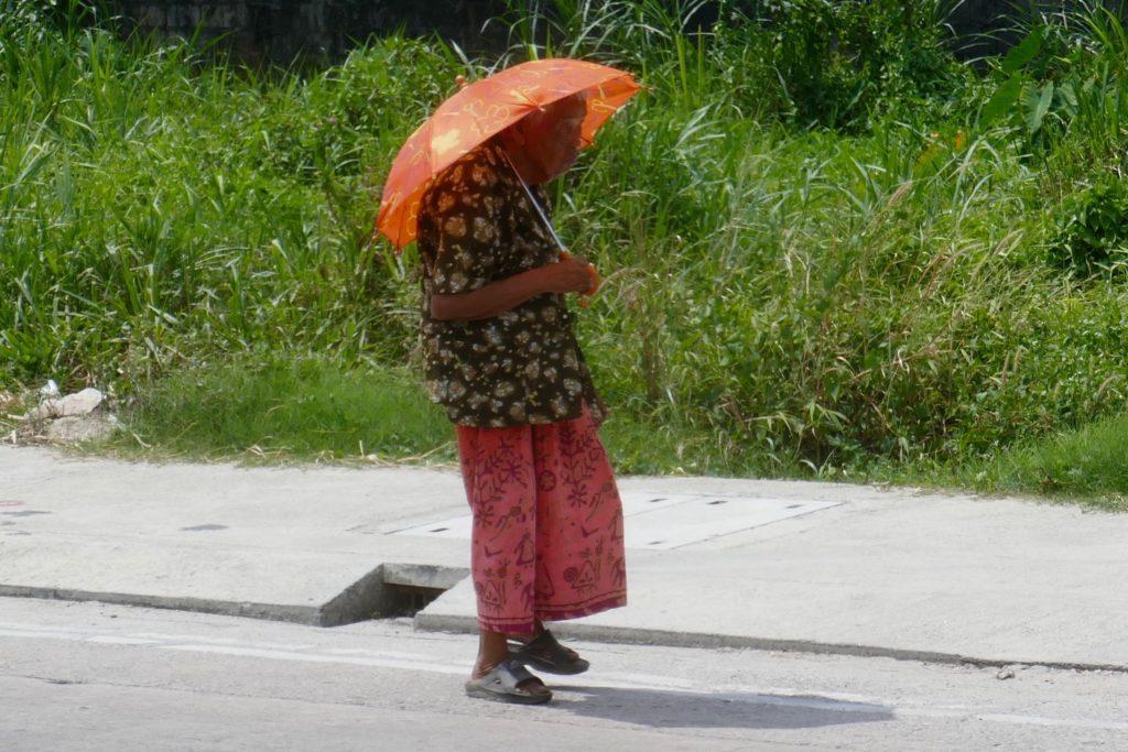 Menschen in Ranong. Alte Frau mit Schirm in der Mittagshitze.