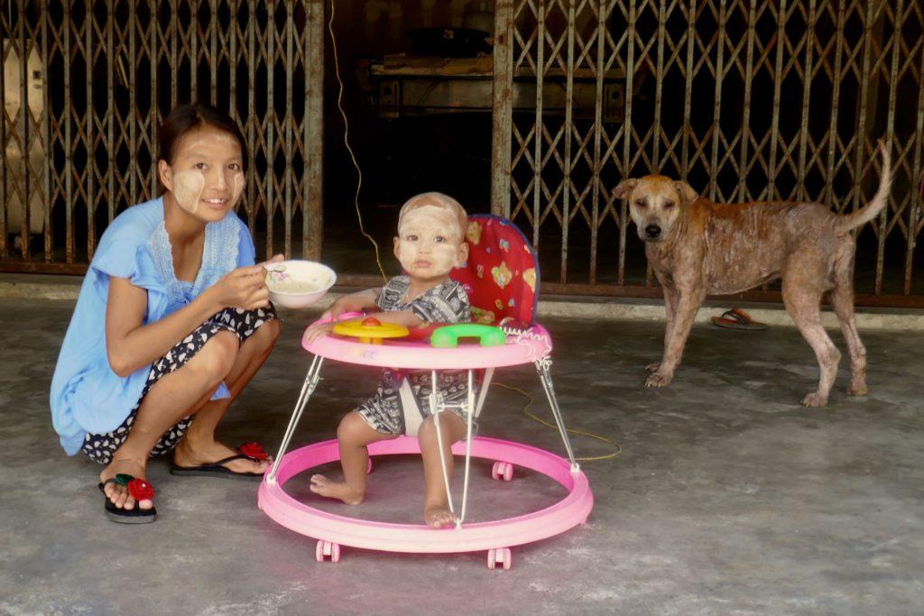 Menschen in Ranong. Babyfütterung mit Hund.