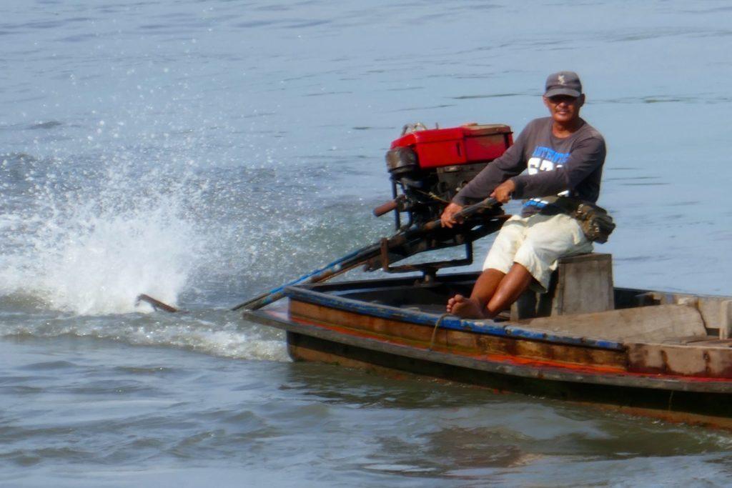 Menschen in Ranong. Motorboot im Hafen von Ranong.