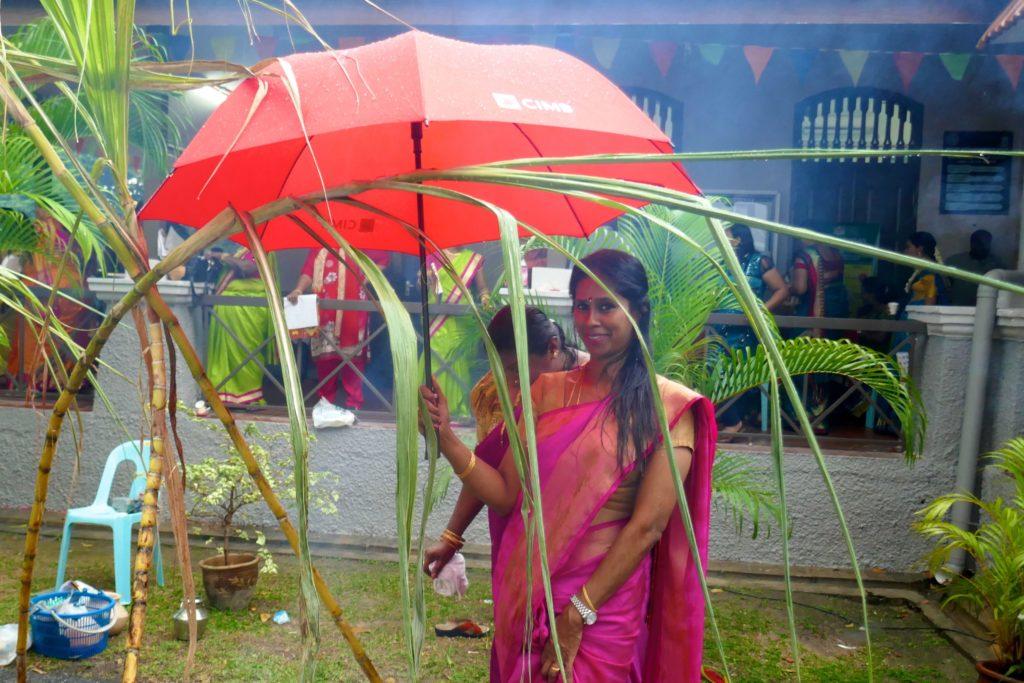 Pongal, indisches Erntedankfest in George Town, Malaysia. Frau mit Regenschirm.