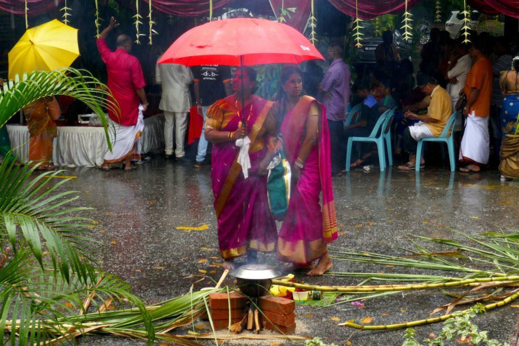 Behütung des köchelnden Reis, während es regnet, bei Pongal in George Town.