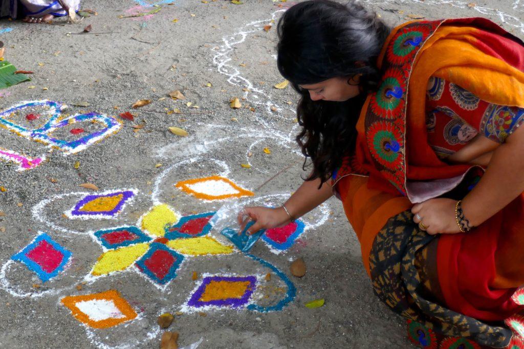 Pongal in George Town, Malaysia. Frau beim Zeichnen eines Kolams.