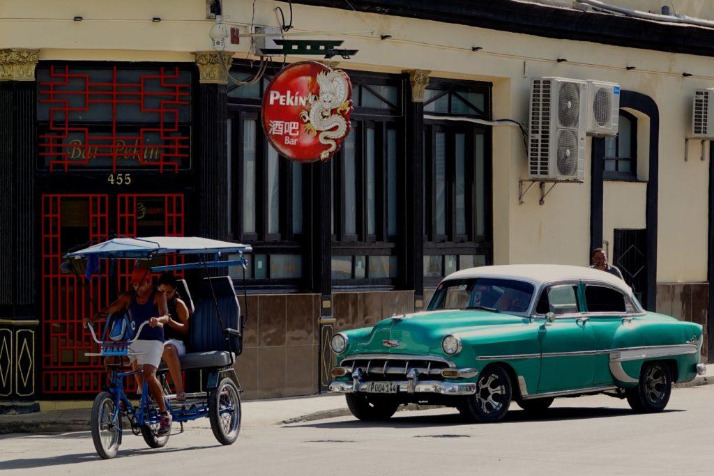 Straßenverkehr in der Calle Zanja und Bar / Restaurant Pekín in Chinatown, Havanna.