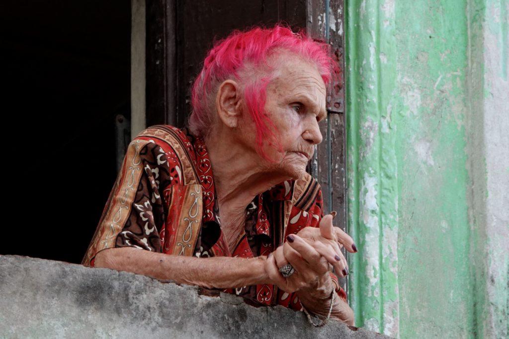 Alte Frau mit roten Haaren in der Altstadt von Havanna.
